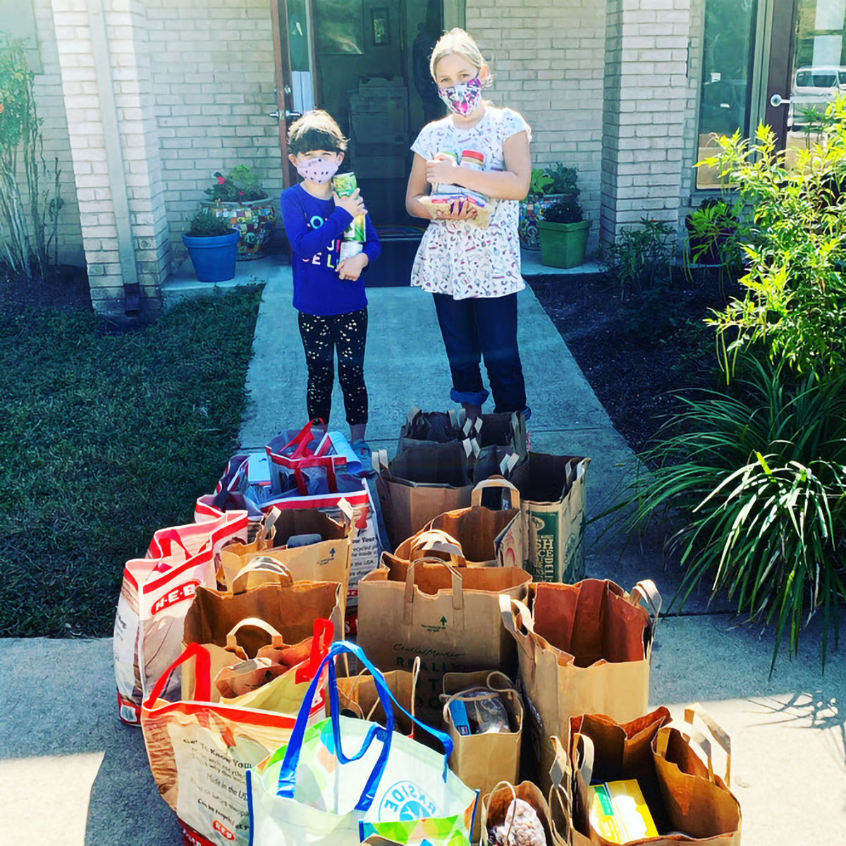 students standing with donated grocery items